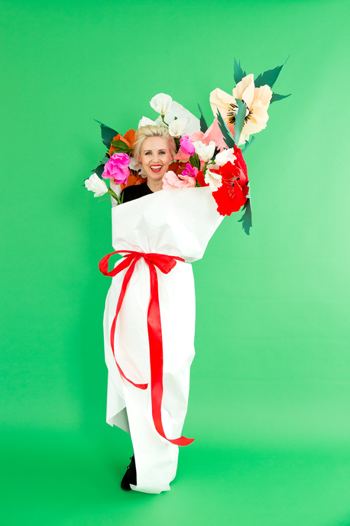 Brittany wearing a bouquet costume with paper flowers and a white paper wrapper against a green backdrop