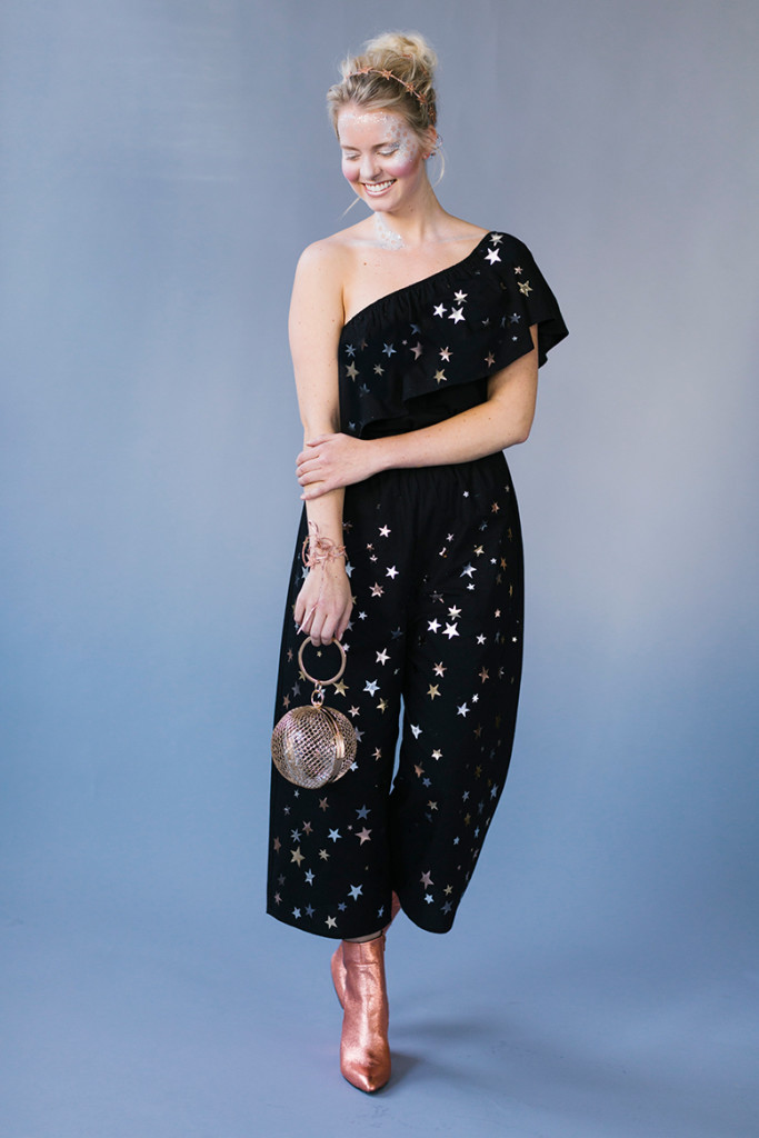 a blonde woman wearing an off-the-shoulder black jumpsuit with silvers stars all over it, sparkly makeup, and a spangled headband against a periwinkle background