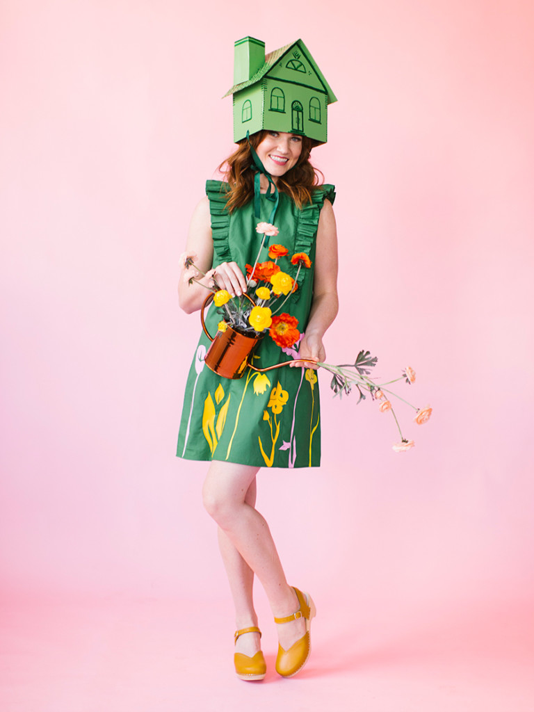 a white woman with brown hair wears a green dress with iron on flowers, a greenhouse hat, and yellow clogs. She's holding flowers and a watering can.