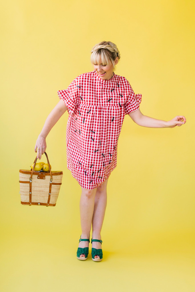 Brittany wears a gingham red dress with ants ironed onto it and holds a rattan picnic bag.