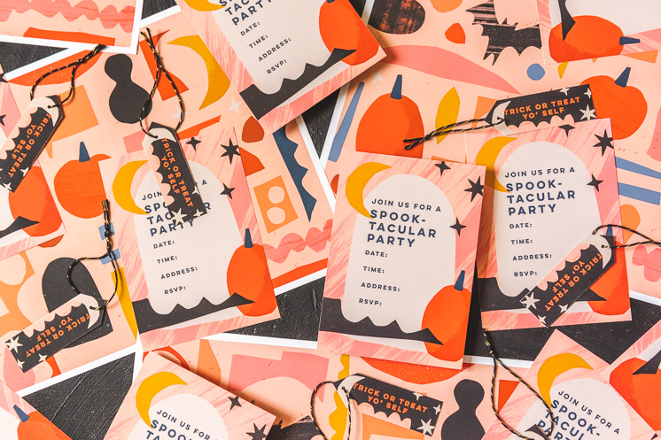 Halloween party invitations, placemats, place cards, and party tags arranged on a table
