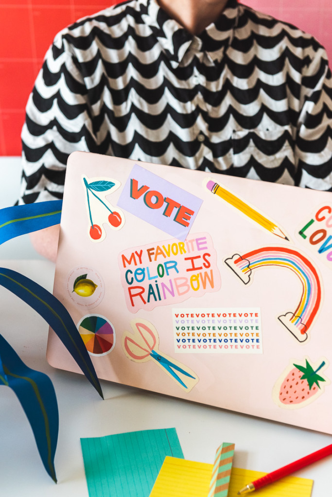 A woman sits behind a laptop, which is covered in rainbow, fruit themed, and office supply stickers.
