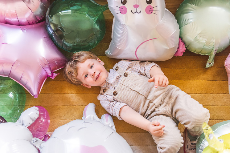 A little boy smiles up at the camera from a yellow rug, where he is lying. He's surrounded by Easter-themed balloons.