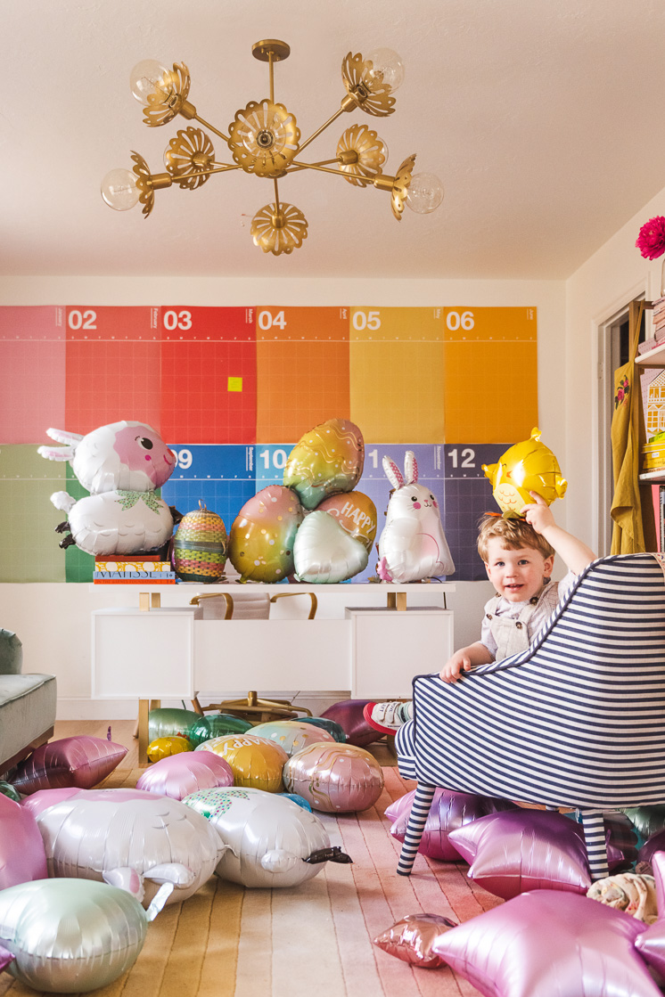 A little boy holds up a chick balloon. He's sitting on a chair in a colorful room strewn with Easter-themed balloons.
