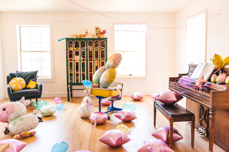 Interior shot of an Easter Scavenger Hunt. Balloons are strewn around the room and string zigzags across the space.