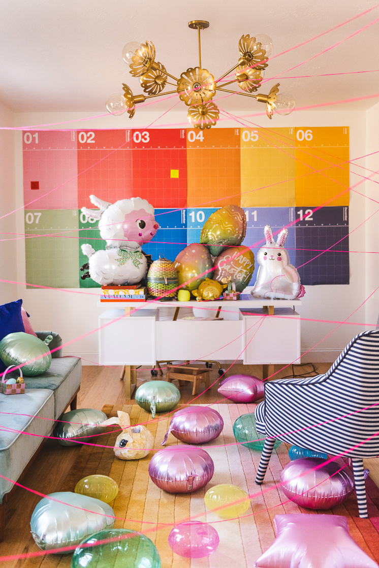 Interior Photo of a colorful room with Easter-themed balloons on the desk and floor, and pink string criss-crossing through the space.