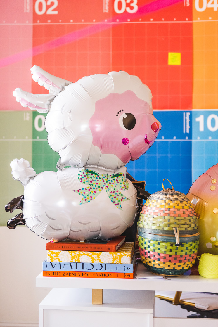 A big Easter lamb balloon rests atop a stack of colorful books in a colorful interior space.
