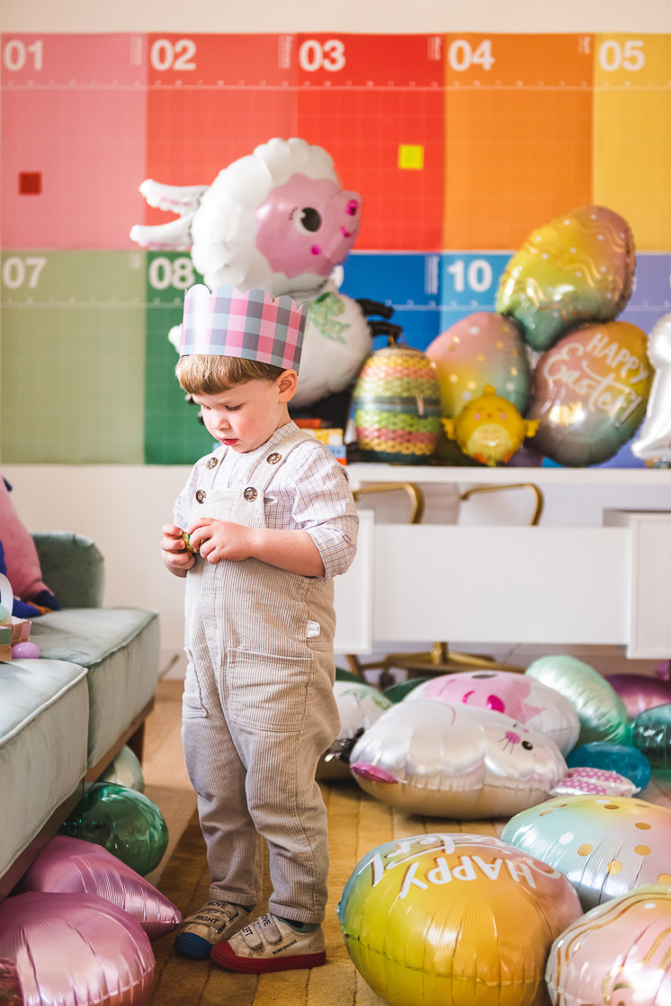 A little boy in a pink and blue Easter crown stands in a colorful room filled with Easter-themed balloons.