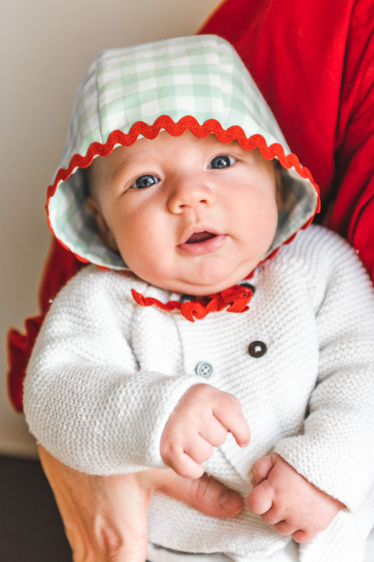 Baby wearing green and red bonnet looks into the camera