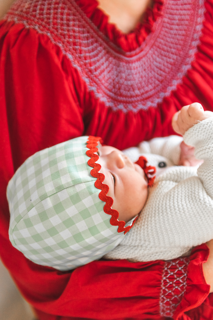 baby in green and red bonnet held by woman in a red dress