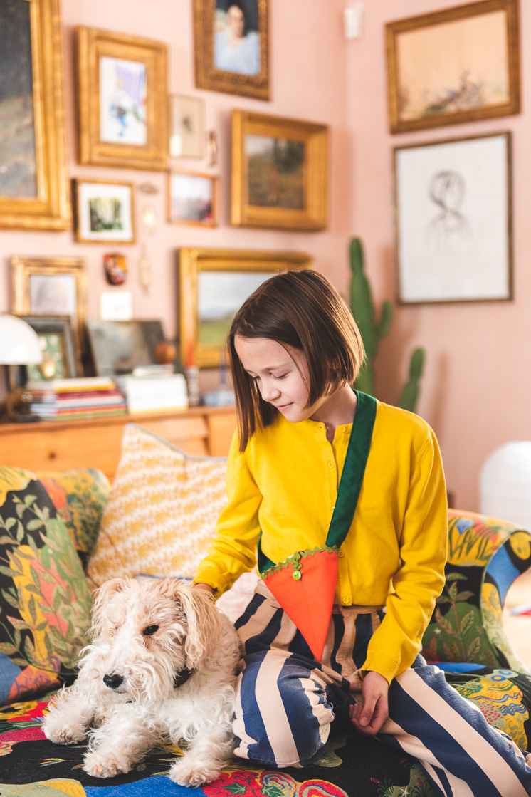 A girl in a yellow shirt pets a dog while wearing a fabric carrot bag over her shoulder.