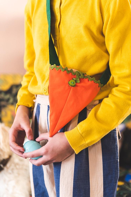 girl in a yellow shirt wears a fabric carrot bag across her body.