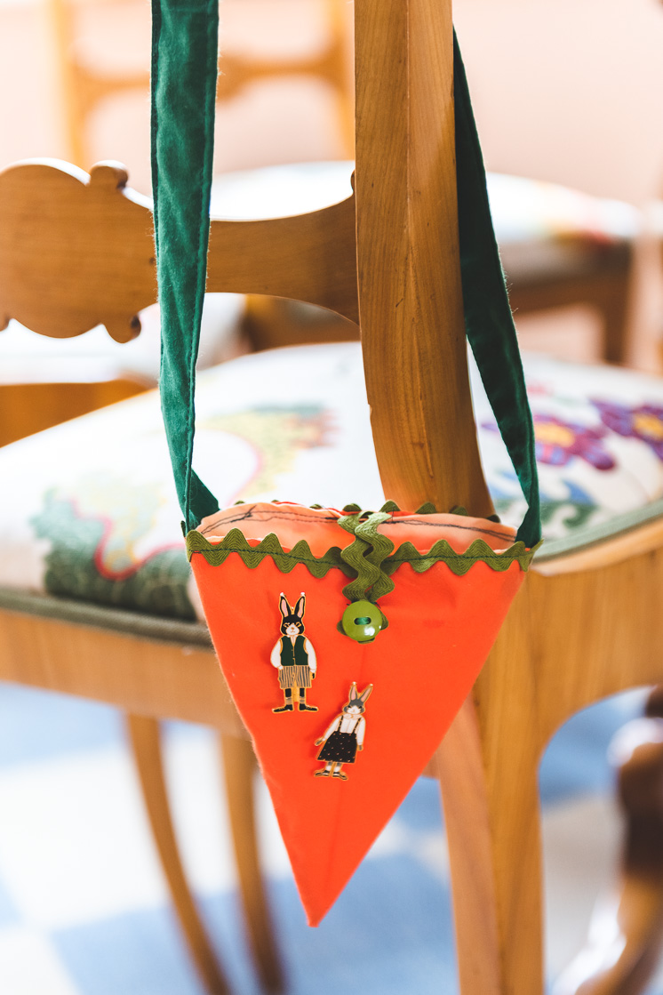 A carrot bag hangs on the back of a chair with two easter bunny pins attached to it.