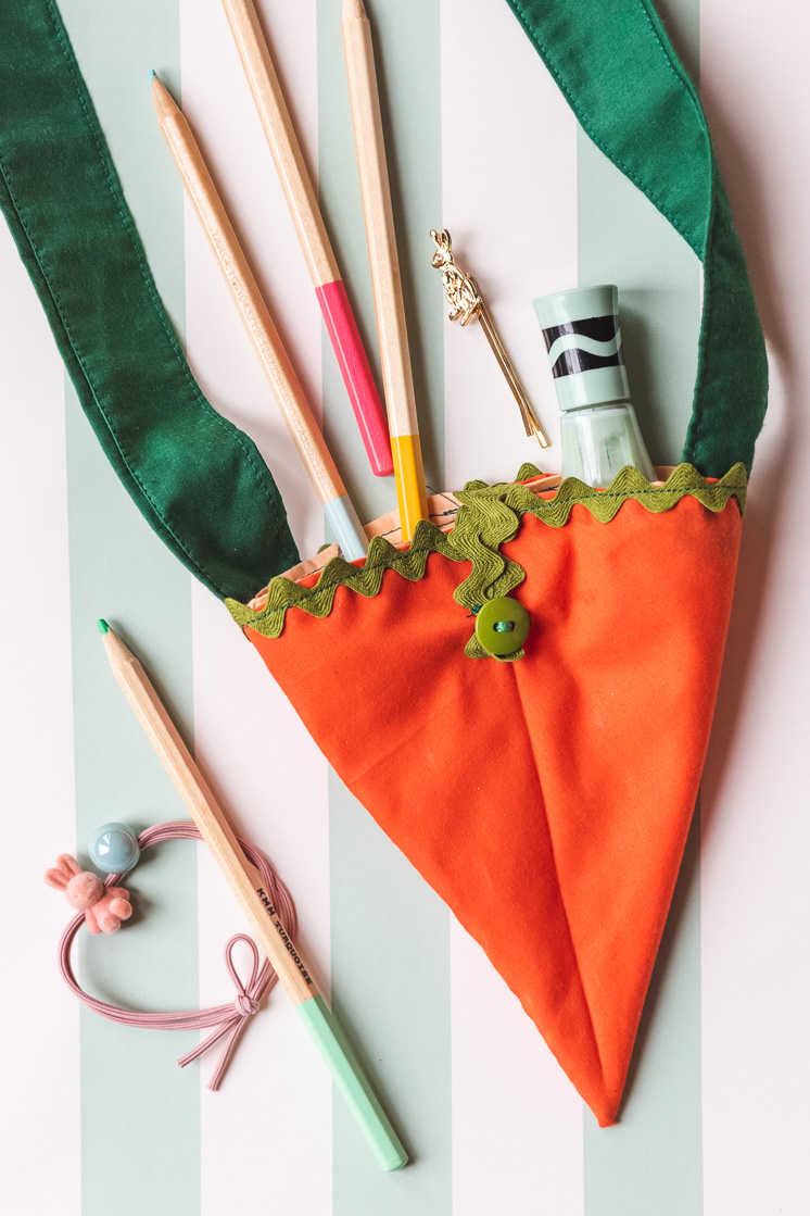 orange fabric carrot bag on a blue and white striped background with art supplies spilling out of it.