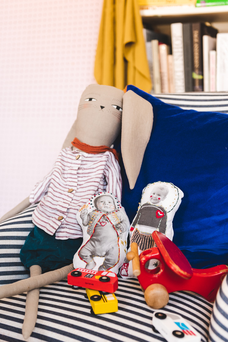 Two embroidered plush dolls on a couch with a plush rabbit and colorful toys.