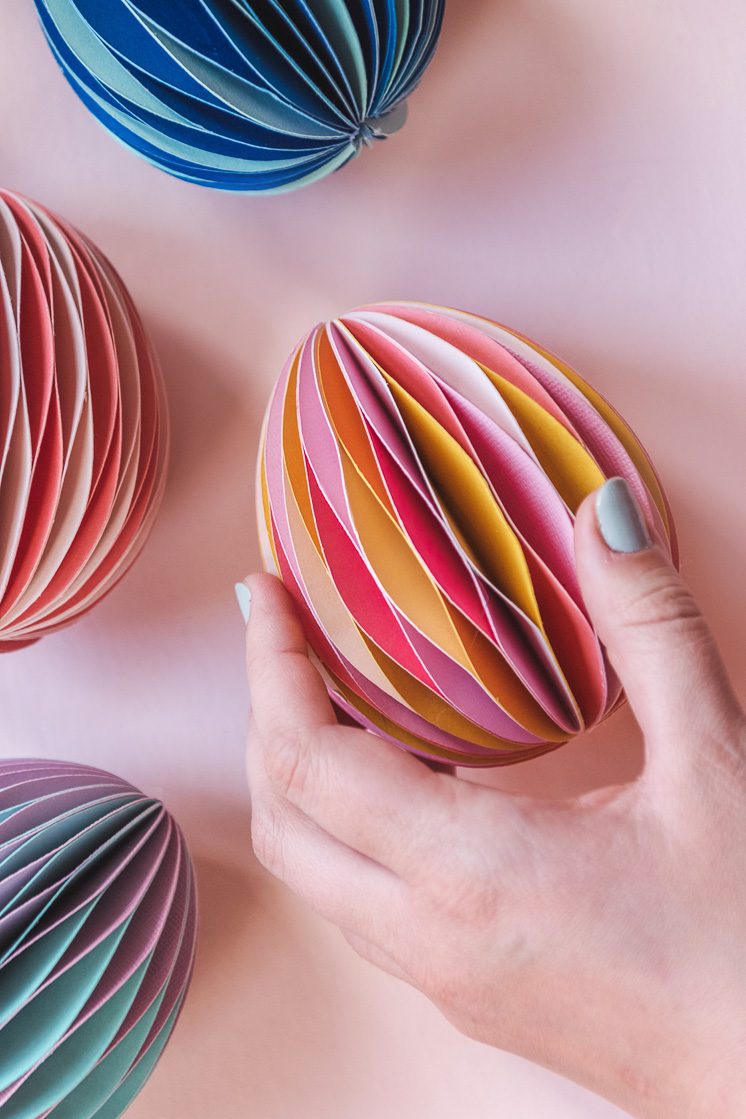 A hand reaches for honeycomb Easter eggs on a blush pink background