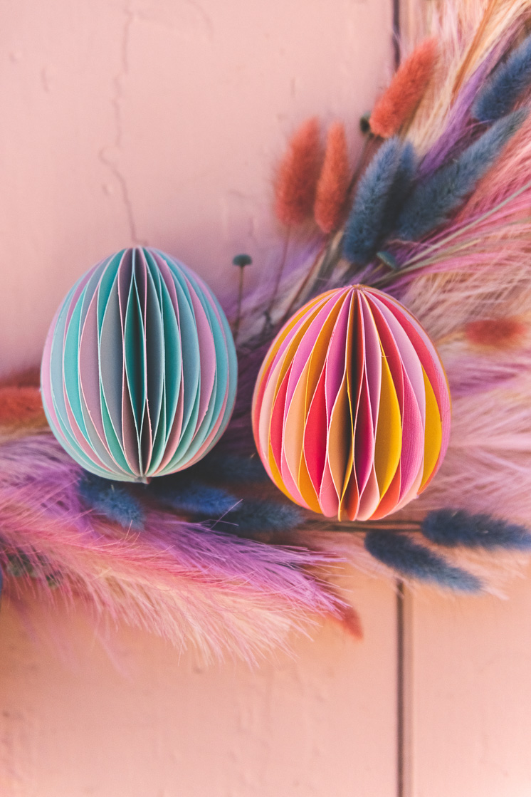 Paper honeycomb Easter Eggs on a pastel floral wreath against a pink wall