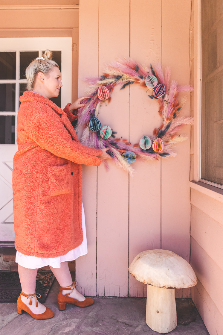 Brittany hangs up a pastel floral Easter wreath on a pink house. She's wearing a persimmon coat, a white dress, and clogs, and a cute wooden mushroom is on the porch.