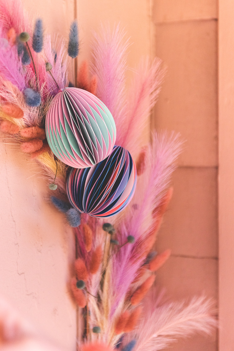 Paper honeycomb Easter Eggs on a pastel floral Easter wreath on a pink wall.