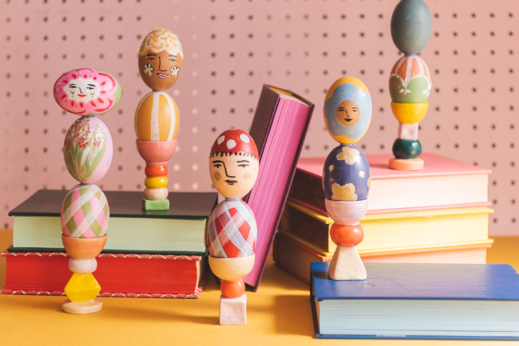 Colorful painted easter egg columns stacked on books against a pink background.