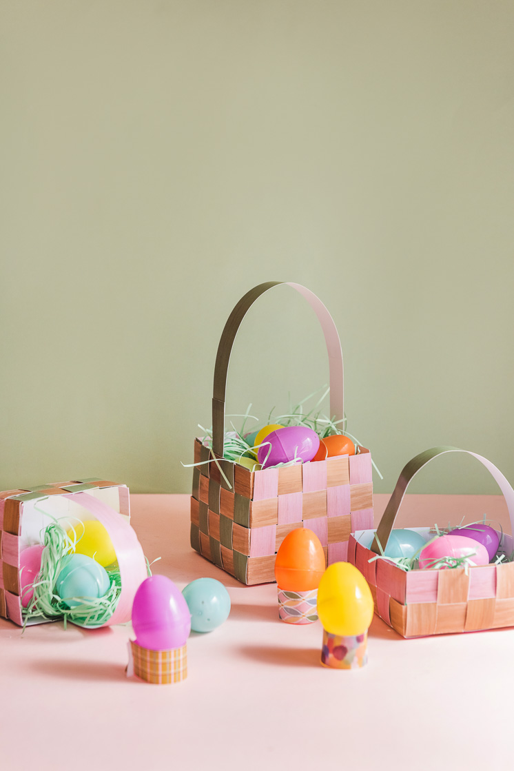 Paper Easter baskets filled with paper grass and plastic eggs against a pink and green background