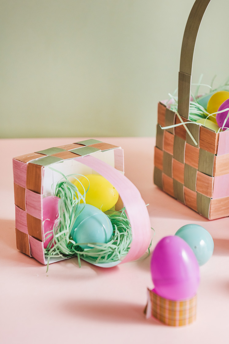 Paper grass and plastic eggs spill out of a paper Easter basket against a pink and green background