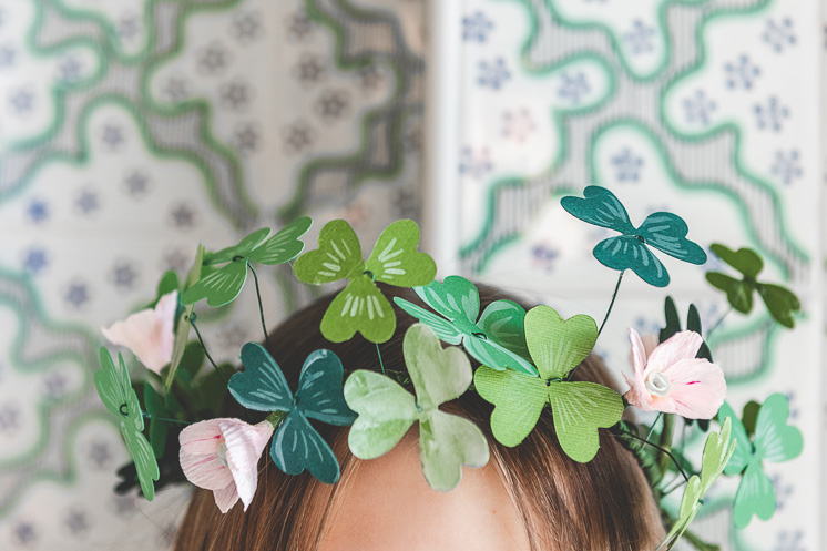 A paper shamrock and flower crown on a brunette girl's head against green and white wallpaper