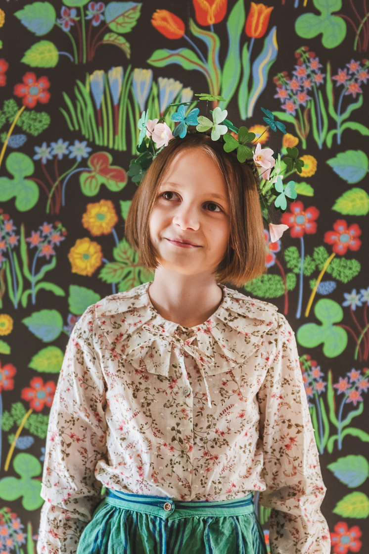 A little girl with brown hair wears a paper shamrock crown and a cream colored floral blouse. The background is bold colored wallpaper.