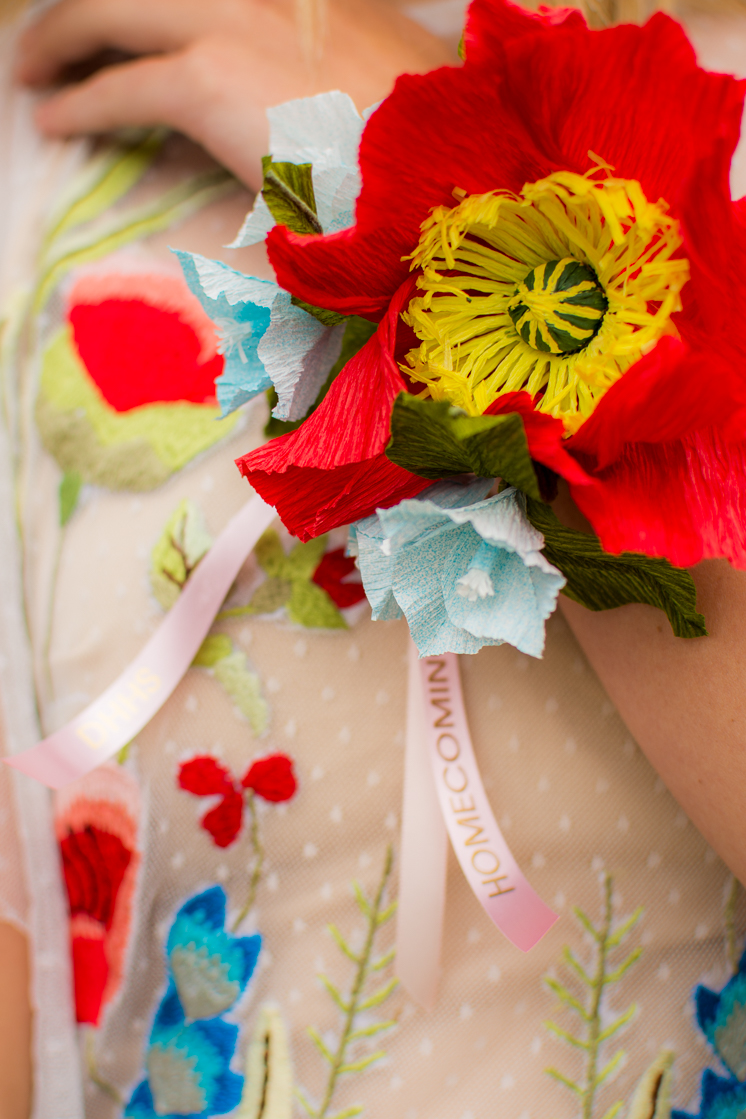 a brightly colored paper poppy corsage