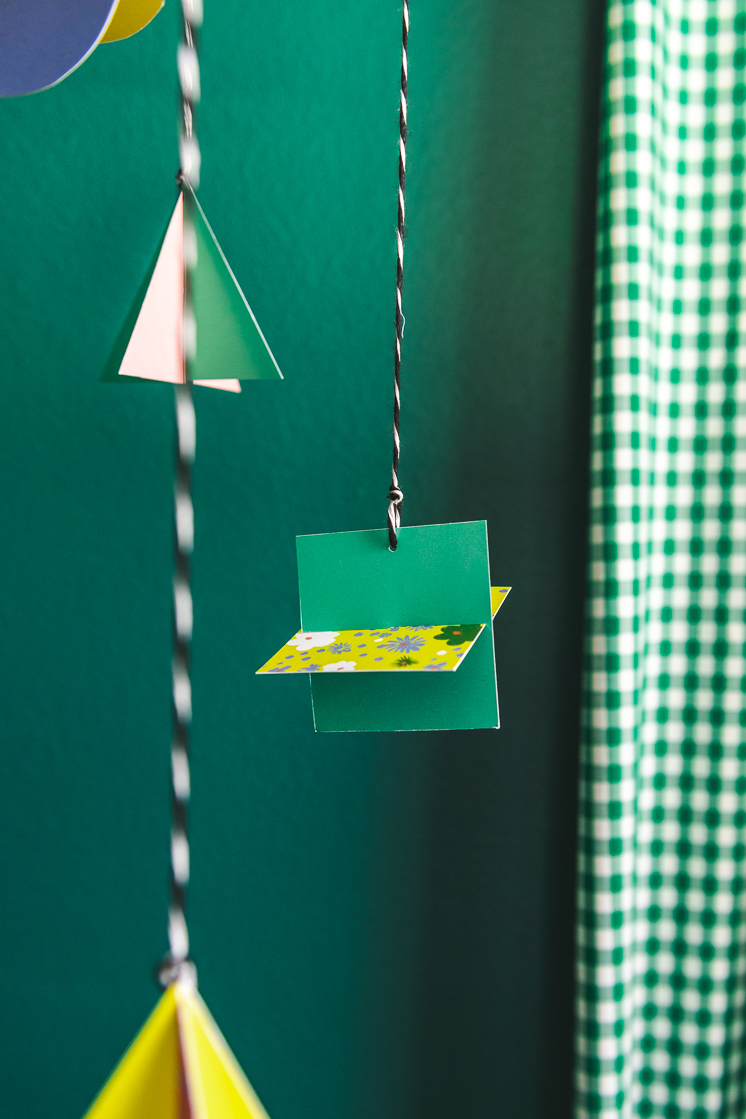 Colorful, geometric paper shapes hang from a mobile in a green room.