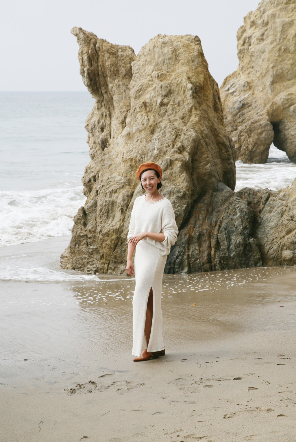 Jeanee stands on a beach wearing a white top and a white skirt. She's looking at the camera and smiling.