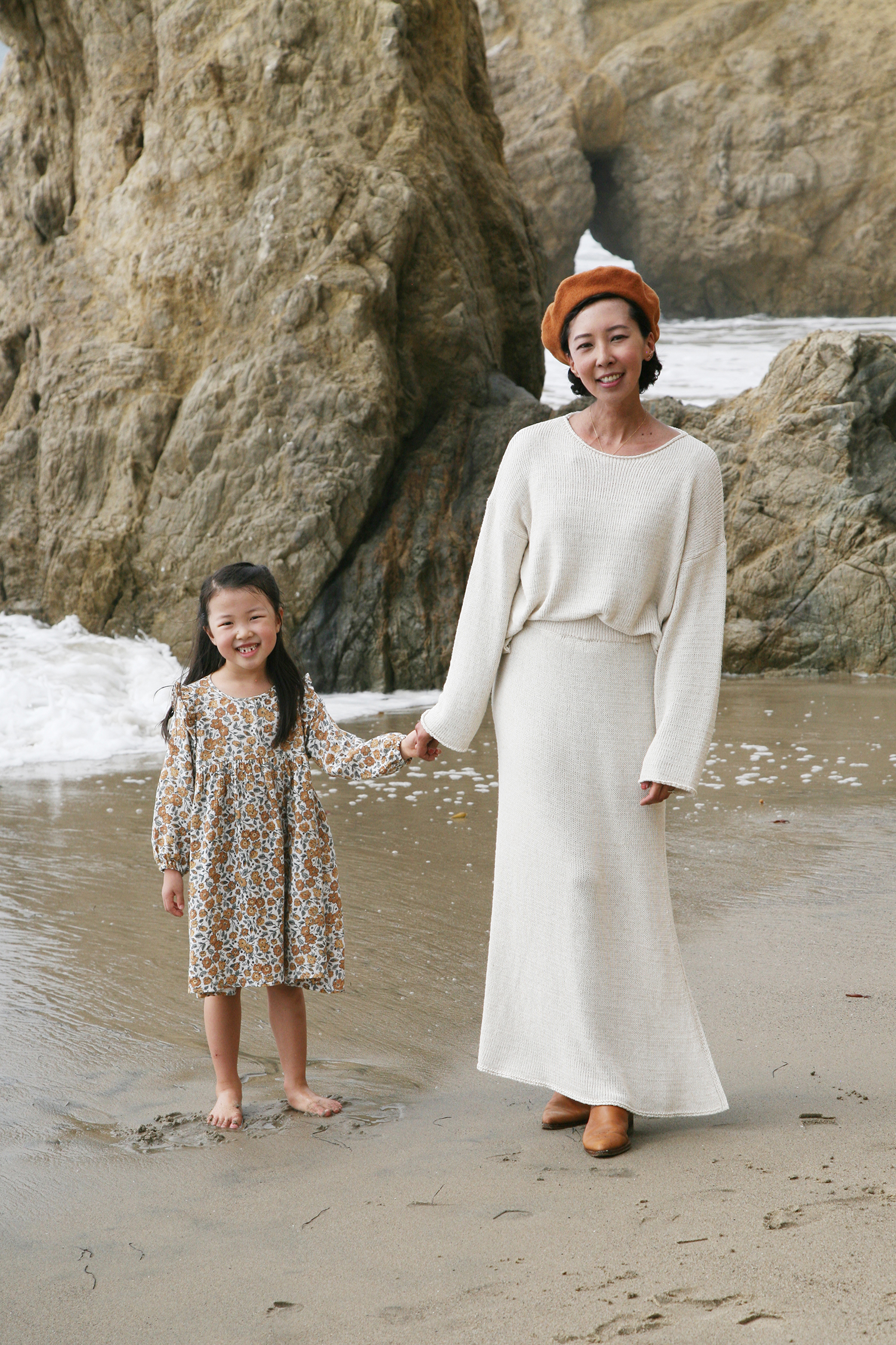 Jeanee and her daughter are standing on a beach. They're holding hands and smiling at the camera.