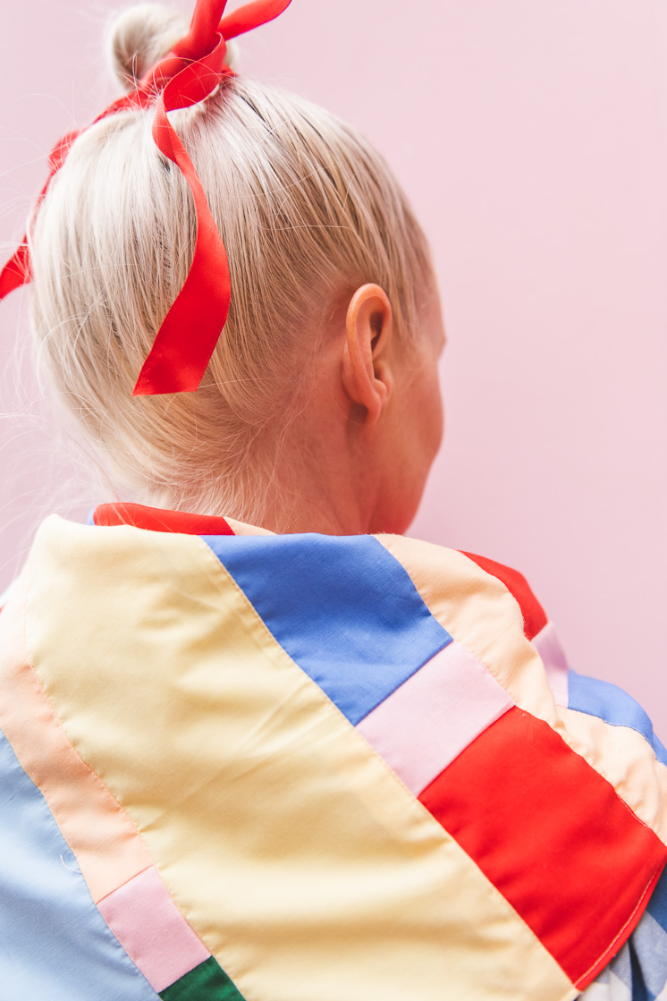 Brittany wearing a patchwork bandana over her shoulders. Her hair is tied up with a bright red ribbon and she's in front of a pink backdrop.
