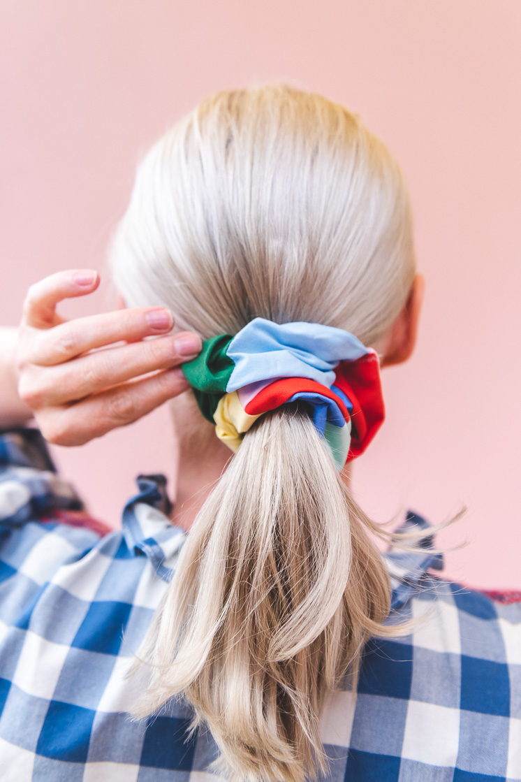 Brittany is wearing a blue and white gingham shirt and a multicolored patchwork scrunchie in her blonde ponytail. She's standing in front of a blush pink wall.