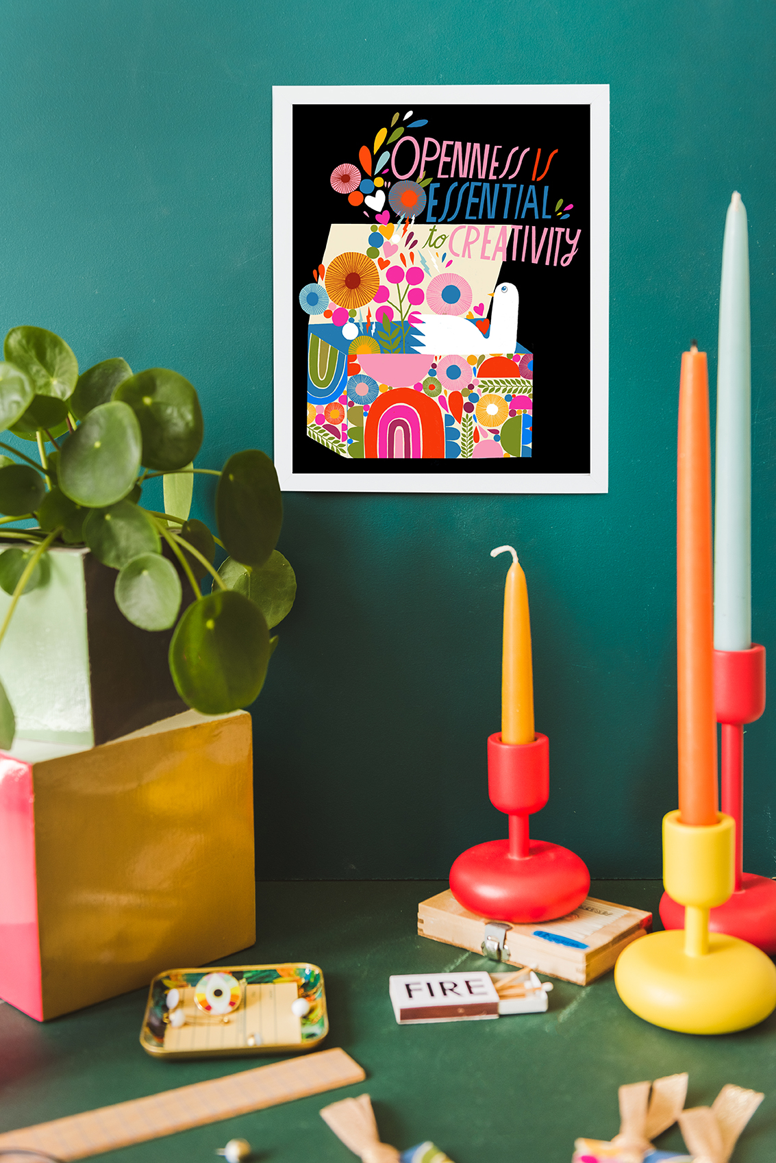 "Colorful art print with the words ""openness is essential to creativity"" among brightly-colored candlesticks and plants in a green space."