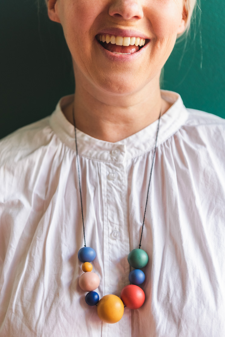 Brittany smiles against a forest green background. She's wearing a white dress and a colorful beaded necklace.