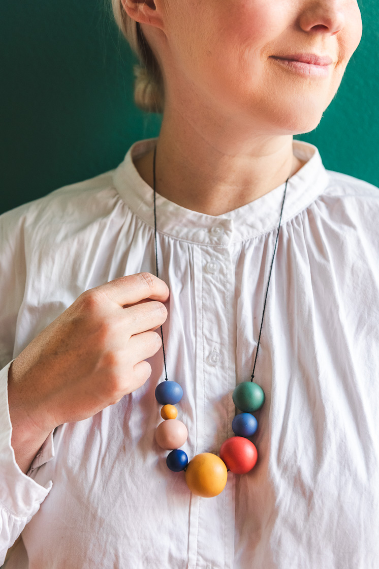Brittany is wearing a white blouse and a rainbow colored clay necklace. She's standing against a green wall.
