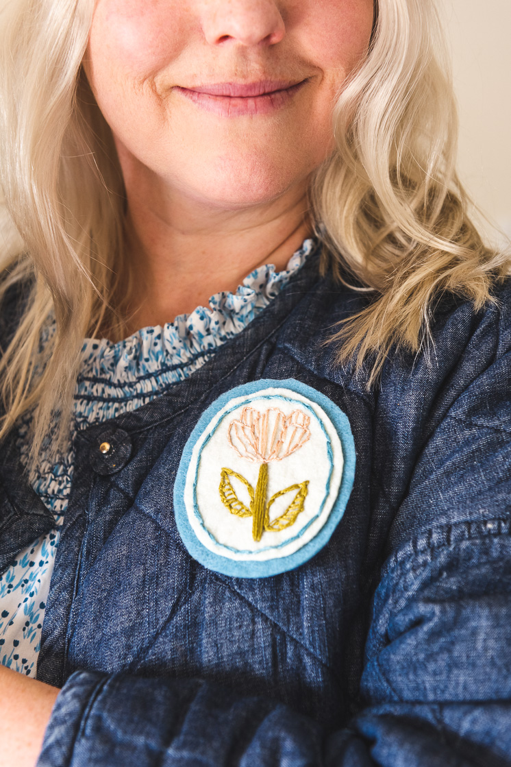 Brittany is smiling at the camera wearing a dress with a ruffled collar and a chambray quilted jacket. She's sporting her embroidered floral brooch.