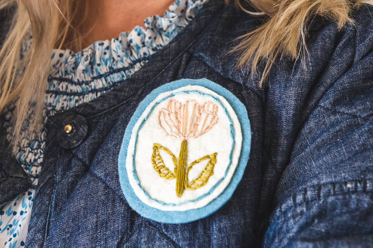 Closeup of the embroidered floral brooch on Brittany's chambray quilted coat.