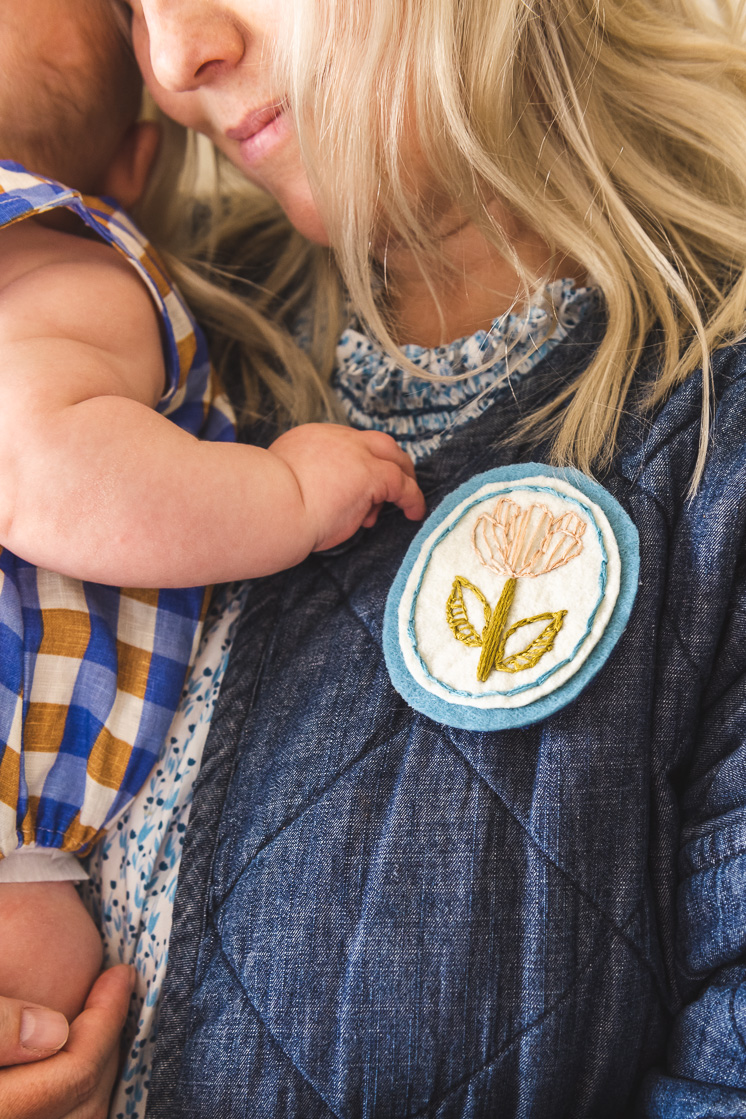 Brittany is sporting her embroidered floral brooch and holding baby Felix.