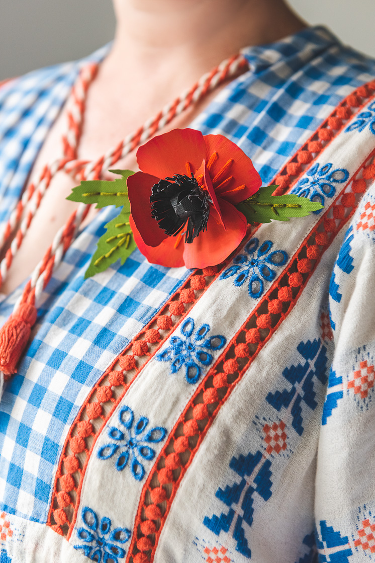 Brittany wears a paper poppy with accenting embroidery on a woven blouse.