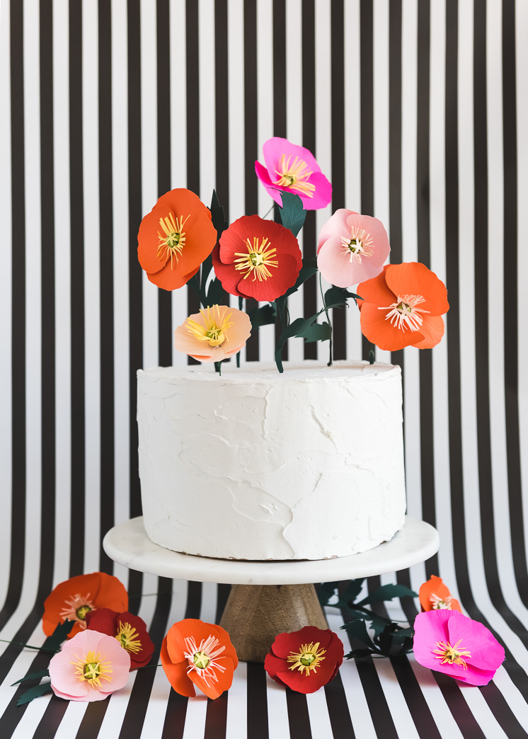 Paper poppies in bright colors as a cake topper against a striped background