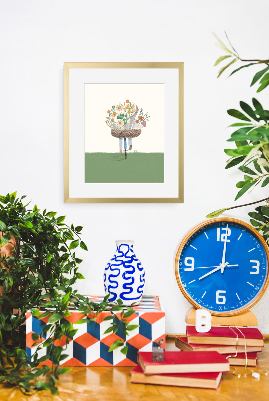 Art print of a person riding a bike with a basket full of flowers on a white wall with plants, a clock, and vases around.
