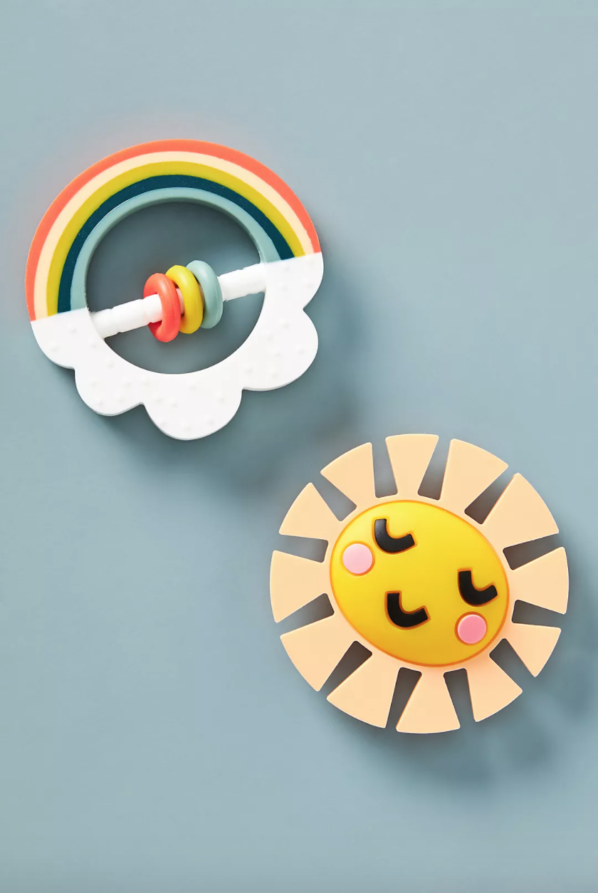 Silicone teether toys on a baby blue background. One is a smiling sun, one is a rainbow with a cloud.