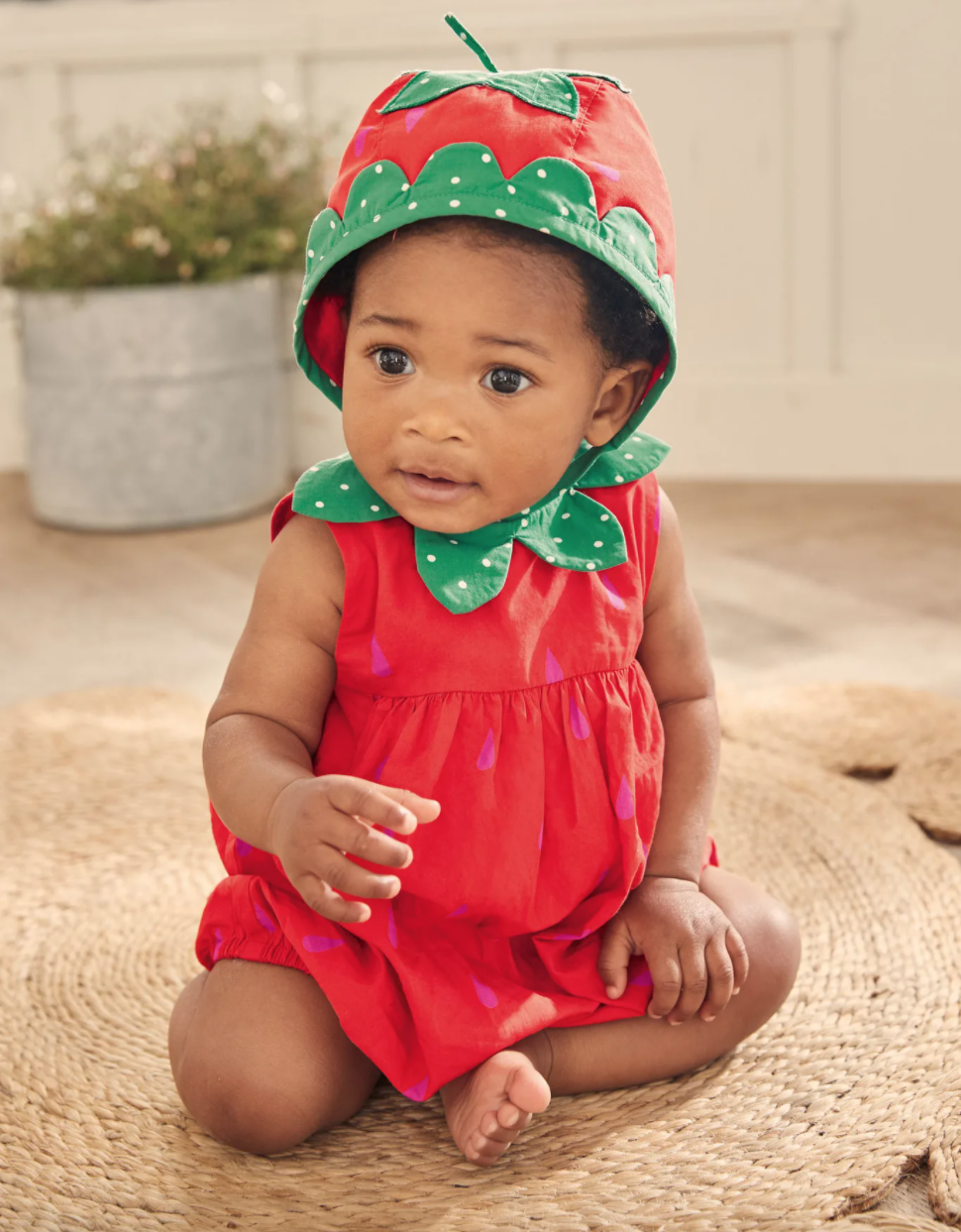 Baby wearing a strawberry bubble romper and a matching hat while sitting on a rug.