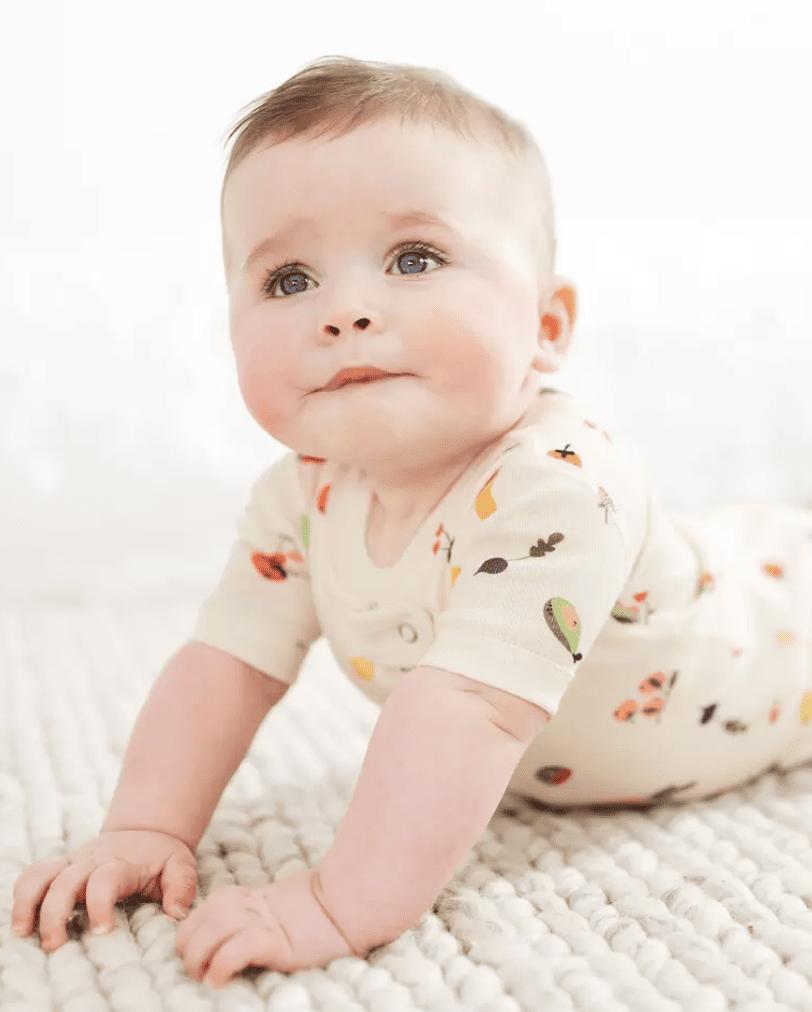 Baby wearing a short-sleeved veggie print sleeper