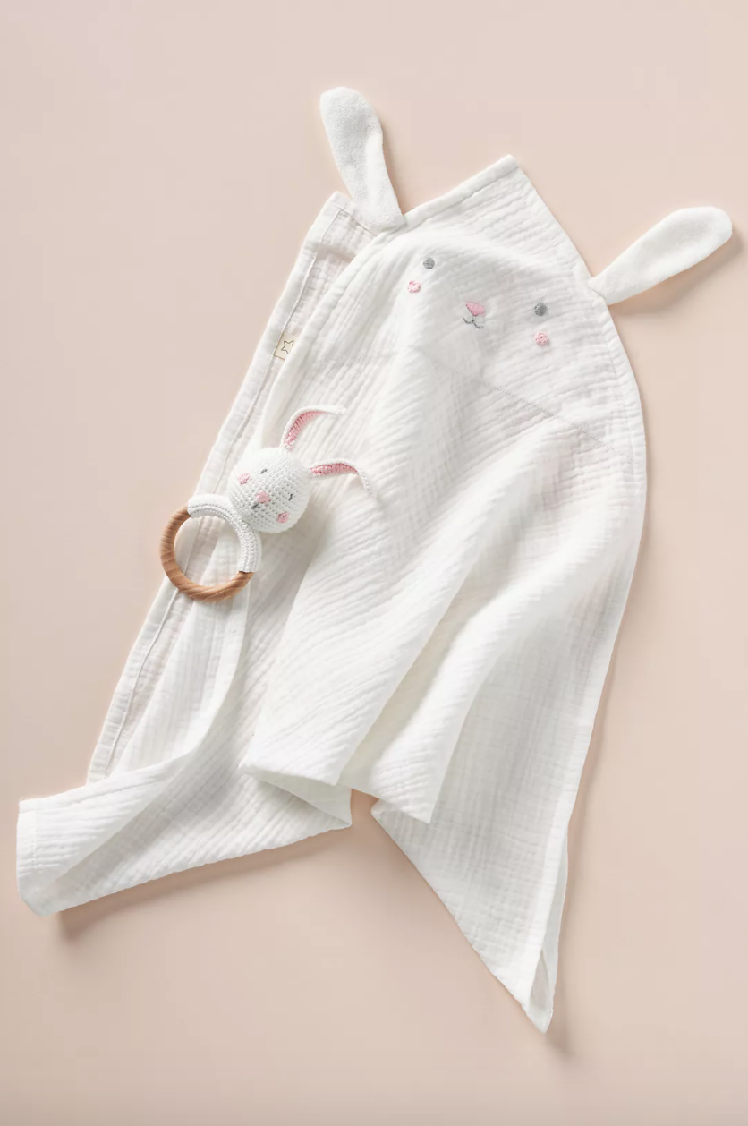 A white bunny swaddle and rattle set on a beige background.