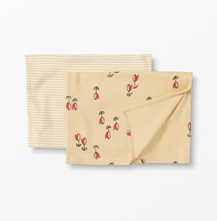 Two burp cloths on a white background. One is yellow and white striped and one is yellow with little red tulips.
