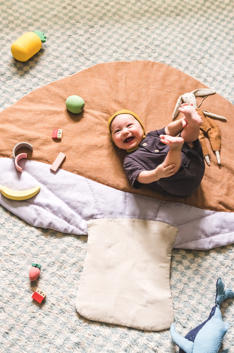 Happy baby lying on a mushroom playmat