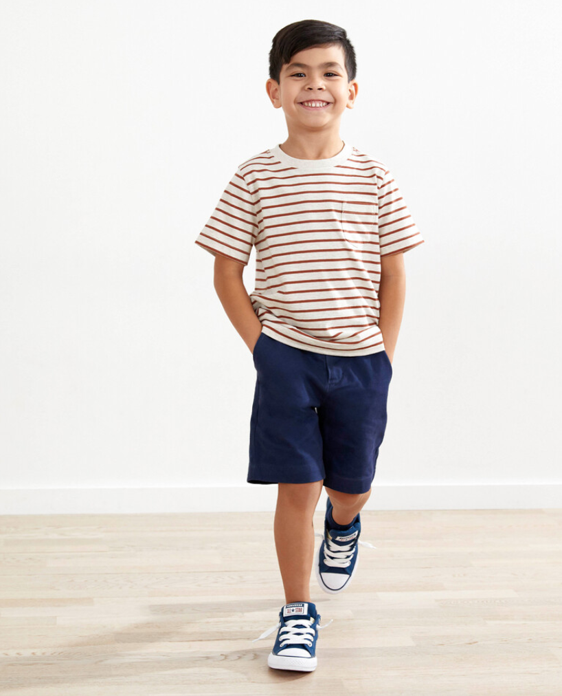 Boy wearing a cream and rust colored striped shirt and navy shorts smiles and walks toward camera